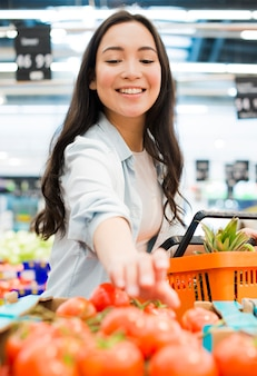 Smiling asian woman picking tomatoes in supermarket