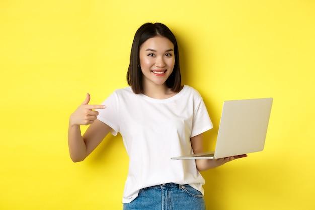 Улыбается азиатская женщина указывая пальцем на свой ноутбук, показывая что-то онлайн, стоя на желтом фоне.