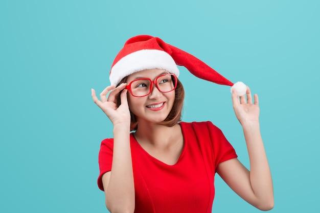 青い背景に分離されたクリスマスサンタ帽子と笑顔のアジアの女性の肖像画。