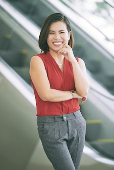 Smiling asian woman posing in front of escalator with finger touching cheek