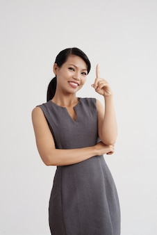 Smiling asian woman posing in studio and holding one finger up