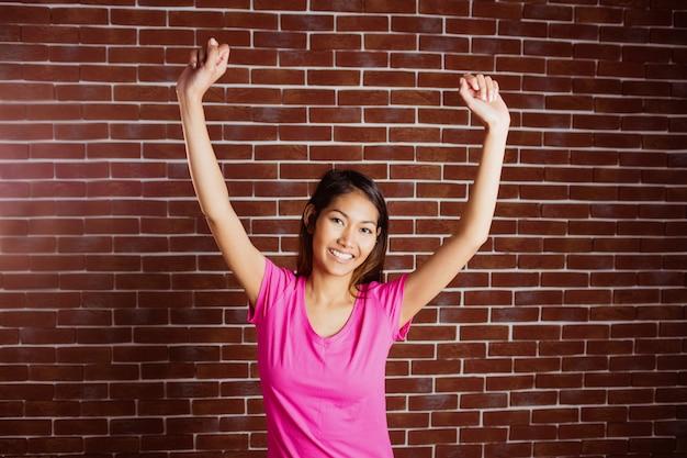 Smiling asian woman raising arms on brick wall
