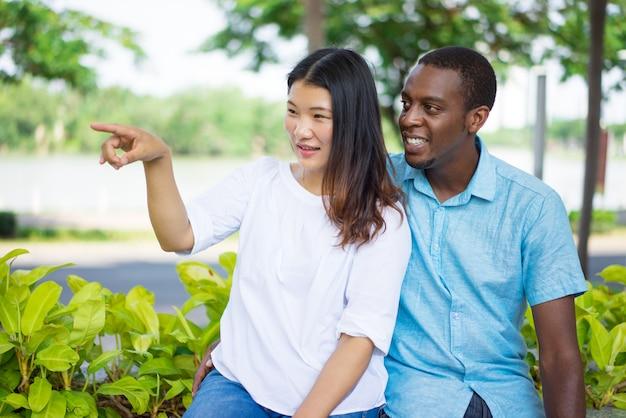 アフリカ系アメリカ人男性への方向を示す笑顔のアジアの女性。