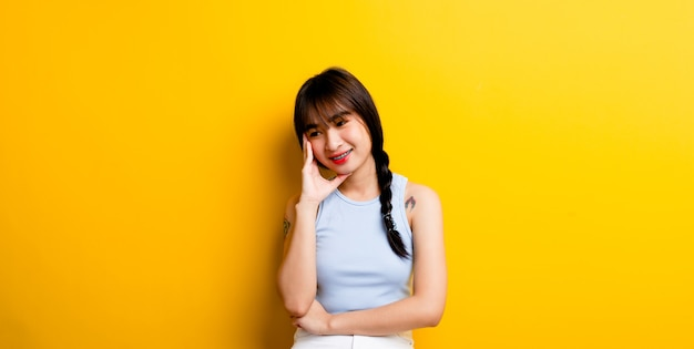 Smiling asian woman showing signs of happiness live happily good health optimistic view of the world on a yellow background