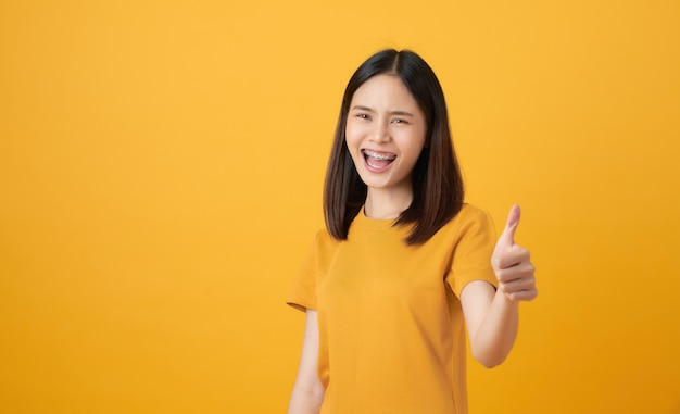 Smiling asian woman and showing thumbs up or like on yellow background.