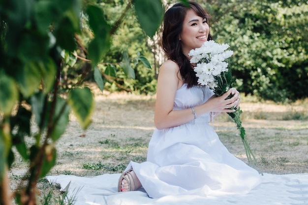 Smiling asian woman sitting on a blanket in a park, holding bouquet of white flowers she's wearing white dress, having picnic in a park, enjoying last warm days of the early fall in tree shadow.