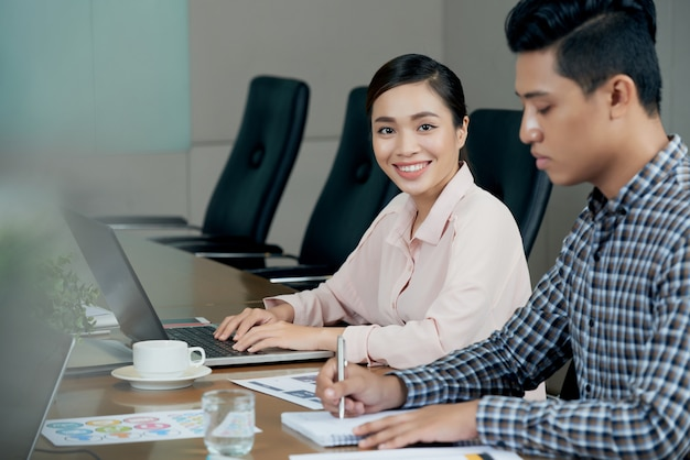 Smiling asian woman sitting at meting table with laptop, amd male colleague writing in notebook