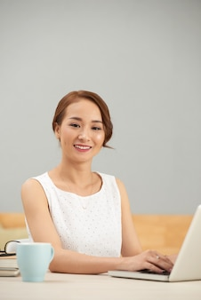 Smiling asian woman sitting at table indoors and using laptop