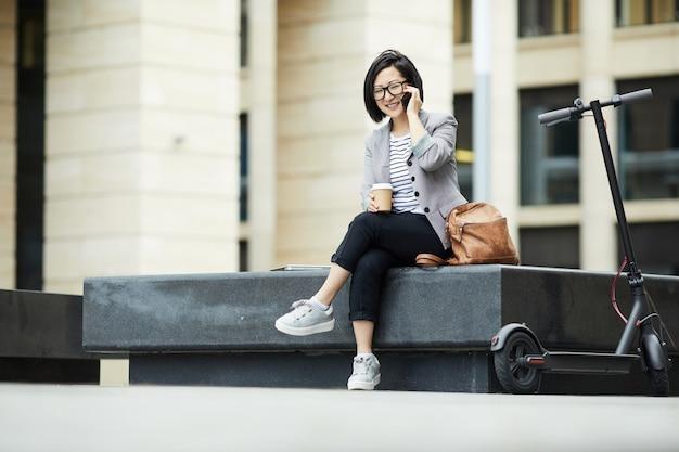 Улыбающаяся азиатская женщина, говорящая по смартфону на открытом воздухе
