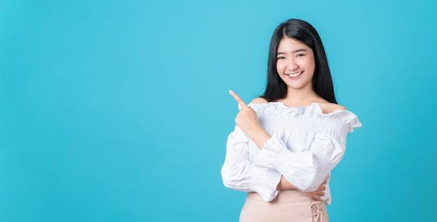 笑顔のアジアの女性が立って、青に人差し指。