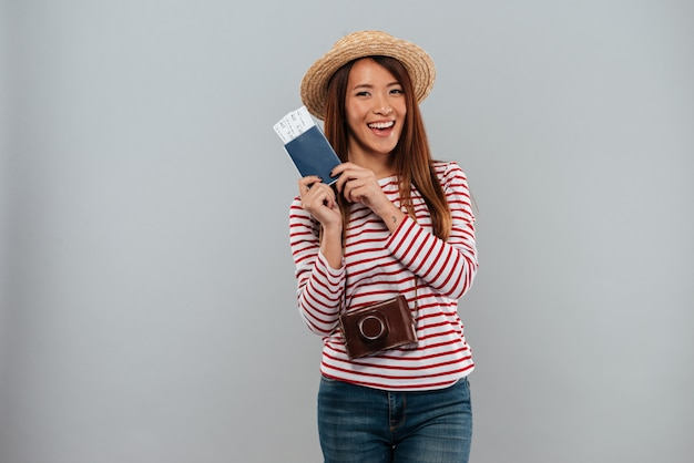 Smiling asian woman in sweater and hat with retro camera