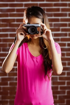 Smiling asian woman taking picture with camera on brick wall