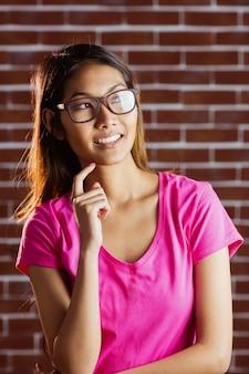 Smiling asian woman thinking on brick wall