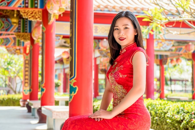 Smiling asian woman in traditional red chinese cheongsam qipao dress