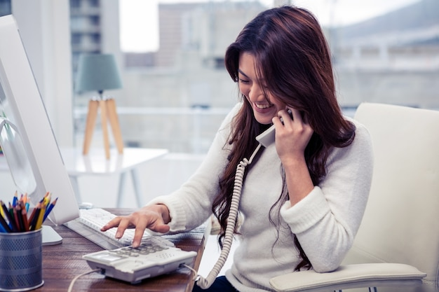 Smiling asian woman typing telephone number in office