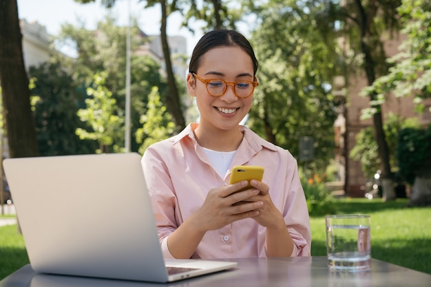 Smiling asian woman using mobile phone shopping online outdoors