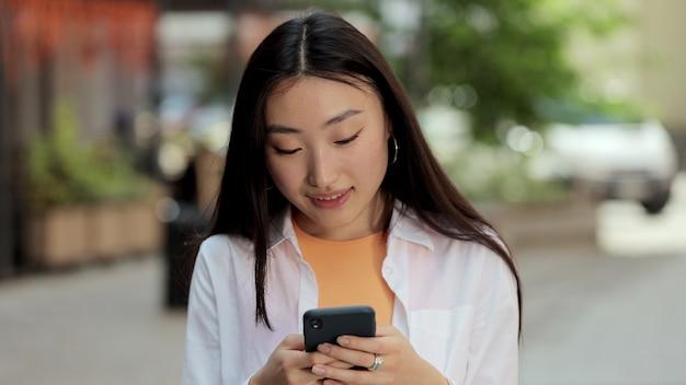 笑顔のアジア人女性が通りを歩き、オンラインでインターネットを閲覧している彼女の電話ソーシャルネットワークを使用します