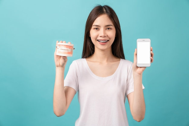 Smiling asian woman wearing braces holding tooth model with smartphone blank screen on blue background, concept oral hygiene and health care.