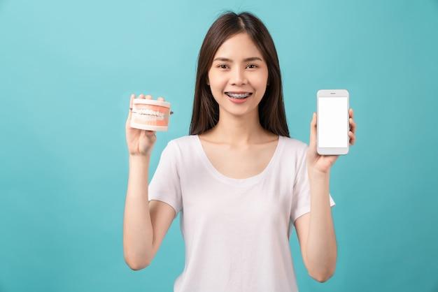 치아 모델을 파란 배경에 스마트폰 빈 화면으로 들고 교정기를 착용한 웃고 있는 아시아 여성, 개념 구강 위생 및 건강 관리.