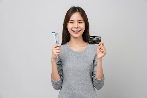 Smiling asian woman wearing braces with tooth and holding toothbrush and dentist tool, credit card on grey background, concept oral hygiene and health care.