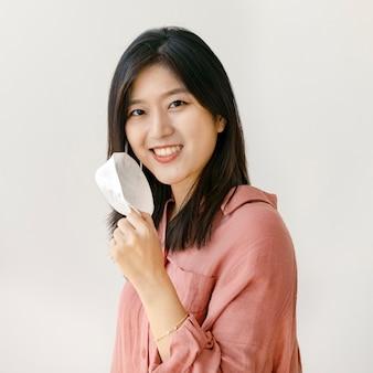 フェイスマスクと笑顔のアジアの女性