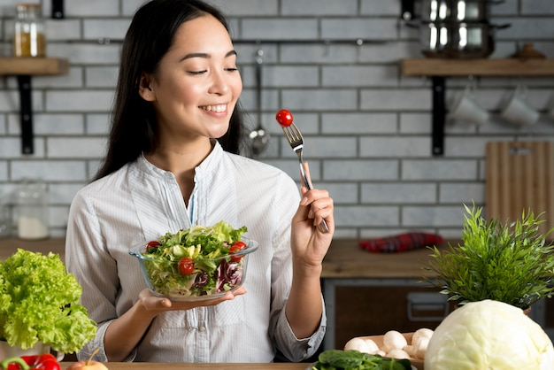 Smiling asian woman with healthy salad in kitchen
