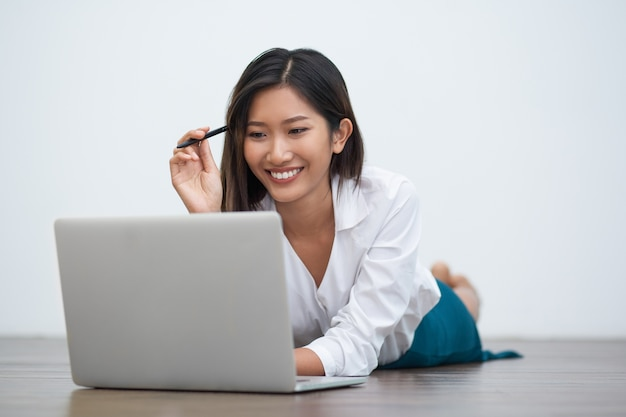 Smiling asian woman working on laptop on floor Free Photo