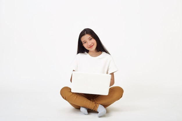 바닥에 앉아 다리를 꼬고 노트북 컴퓨터 작업을 하는 웃고 있는 아시아 여성, 흰색 배경, 학교 개념으로 돌아가기