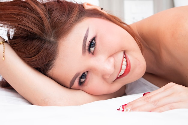 Smiling asian women on bed