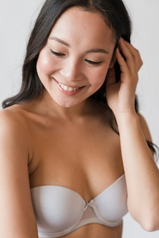 Smiling asian young brunette in bra touching hair
