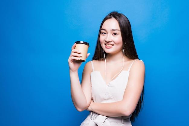 青い壁の上に孤立して立っている持ち帰りのコーヒーカップを保持している笑顔のアジアの若い女性