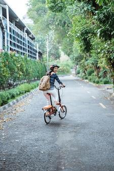 ヘルメットとバッグを身に着けている笑顔のアジアの若い女性は彼の折りたたみ自転車に乗る