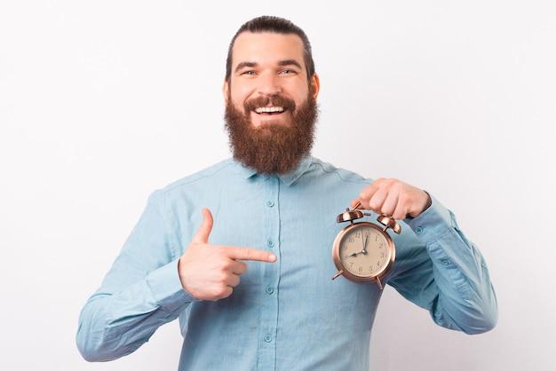 카메라에 미소 수염 난 남자가 알람 시계를 가리키고 있습니다.