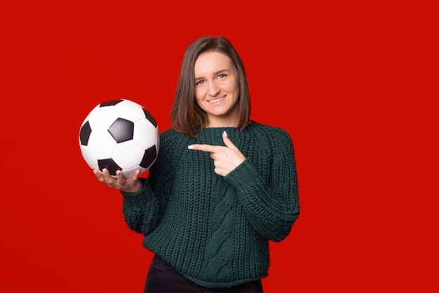 Улыбаясь в камеру, женщина указывает на футбол или футбольный мяч на красном фоне.