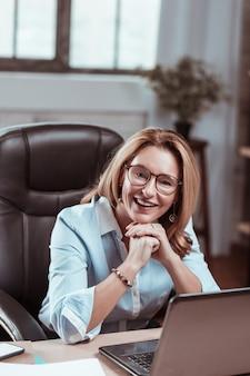 仕事で笑顔。職場で微笑む素敵なイヤリングを着た魅力的な金髪の成熟した女性