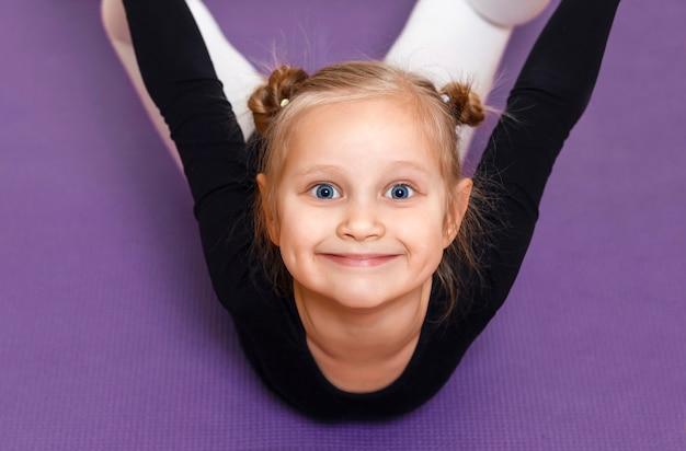 Улыбающийся спортивный ребенок делает растяжку портрет маленького спортсмена на тренировке