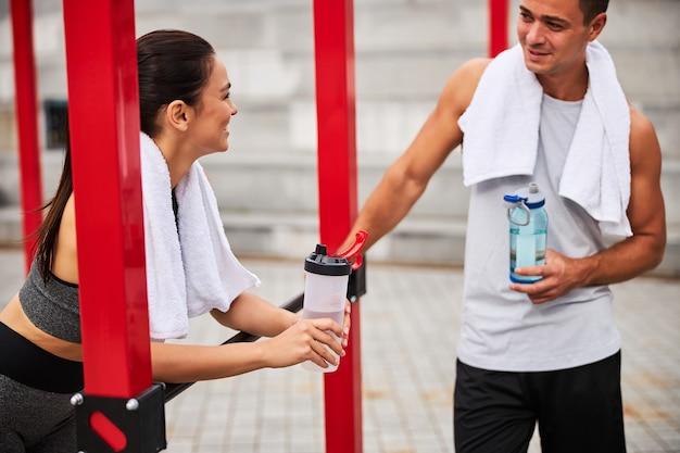 バーや飲料水でトレーニングした後、笑顔のアスリート男性がスリムな女性と話している