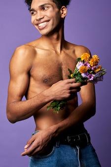 Smiling athletic transgender man with flowers closeup portrait shot naked torso sportsman
