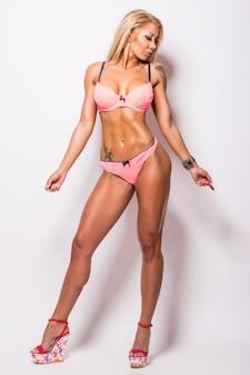 灰色の筋肉を示すピンクのビキニで笑顔の運動選手