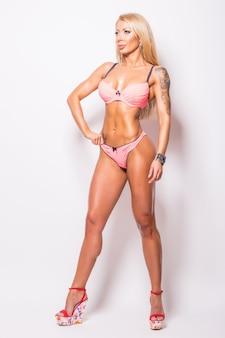 회색에 근육을 보여주는 분홍색 비키니에 웃는 운동 여자