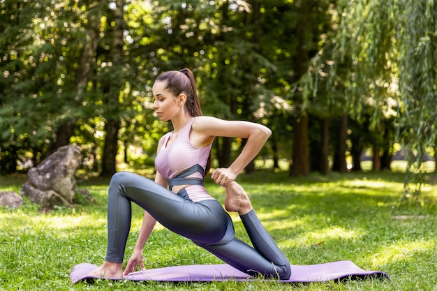 Smiling athletic woman is doing yoga