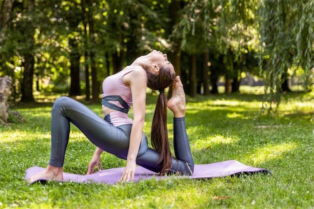 Улыбающаяся спортивная женщина занимается йогой