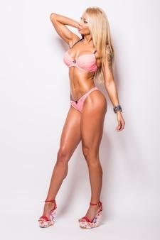 Sorridente donna atletica in bikini rosa che mostra i muscoli sul grigio