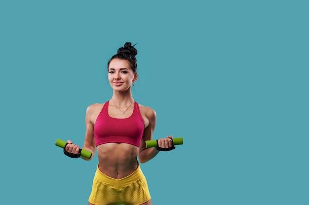 Улыбающаяся спортивная женщина, накачивающая мышцы гантелями на синей поверхности