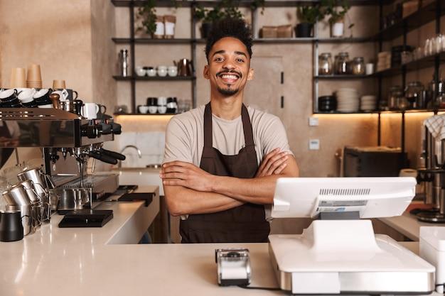 Улыбающийся привлекательный африканский мужчина-бариста, стоящий за прилавком в кафе