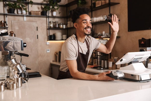 Smiling attractive african man barista standing behind the counter at the coffee shop, greeting customers