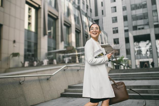 Усмехаясь привлекательная азиатская бизнес-леди в стеклах с газетой встречает коллегу около офисного центра