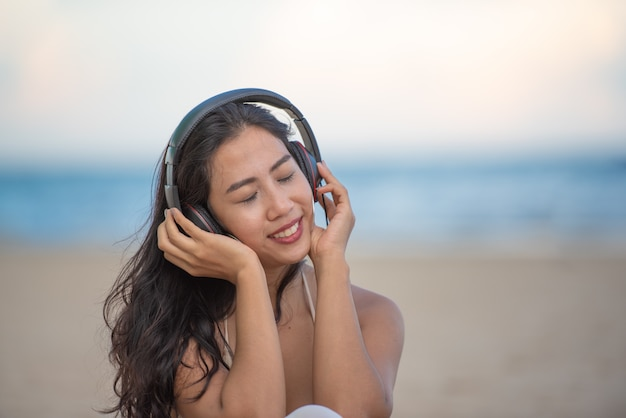 Smiling attractive asian woman with happiness and enjoying on the beach