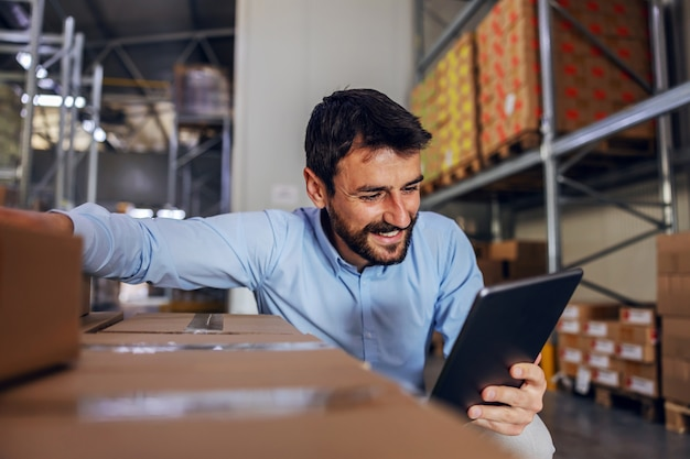 魅力的なひげを生やしたスーパーバイザーがボックスの横にしゃがみ、タブレットを使用して商品を確認する笑顔。