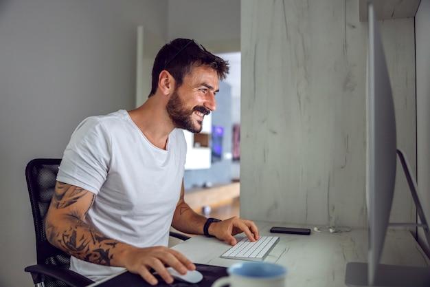 Улыбающийся привлекательный бородатый татуированный фрилансер сидит в домашнем офисе и использует компьютер.